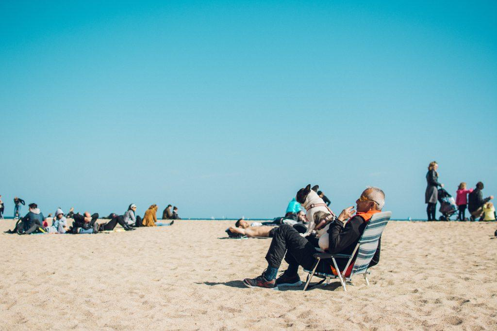 Man sat in a deckchair on a beach with his dog on his lap.