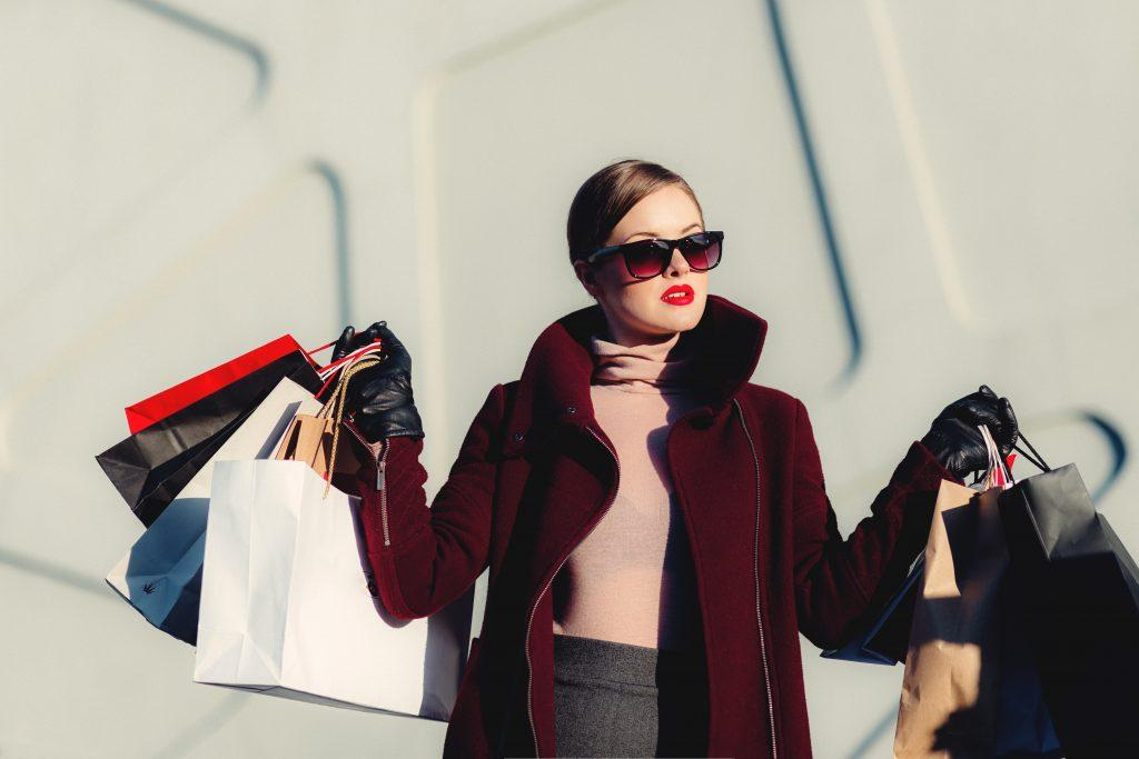 Photo of a fashionable woman holding several bags of shopping.