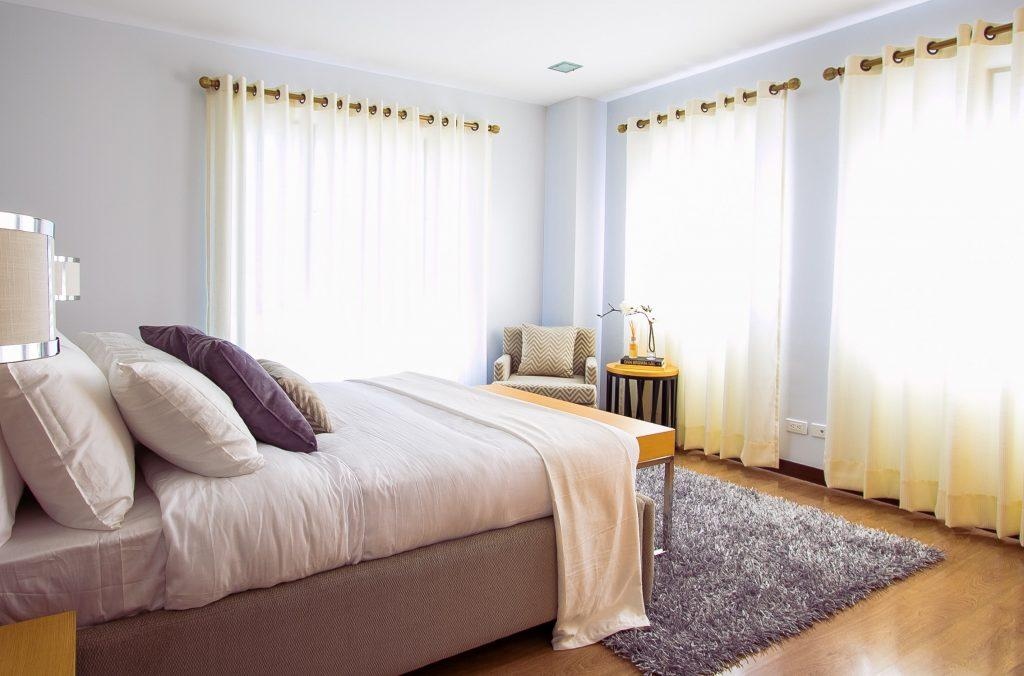 Photograph of a bedroom with a lilac and yellow/off-white theme.