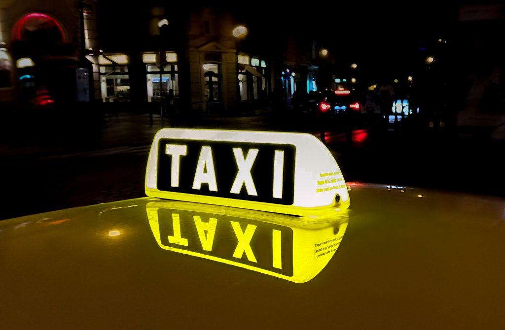 A close-up of a taxi's sign on top of the cab.