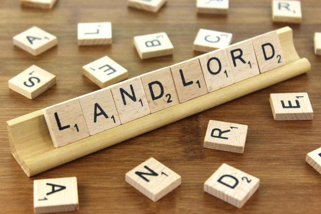 The word 'landlord' written on a Scrabble letter stacker.