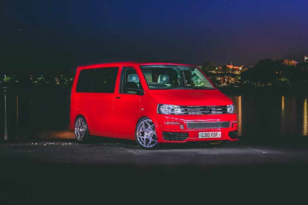 A red Volkswagen van at night.